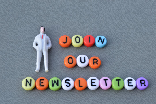 Selective focus  of miniature businessman and alphabet beads written with text JOIN OUR NEWSLETTER. Business concept