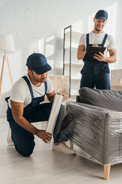 Indian mover in cap holding stretch film roll near sofa and worker with clipboard on blurred background