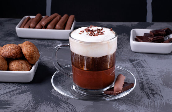 Bicerin, layered Italian coffee drink with chocolate and whipped cream in the glass against the black brick wall