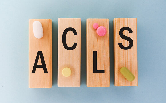 Word ACLS on wooden blocks surrounded with colorful pills. Medical and care concept.