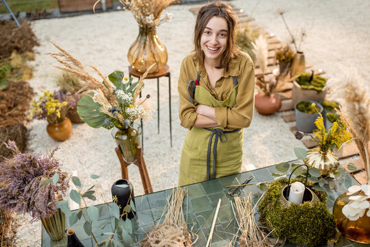 Portrait of a cheerful woman making compositions of dried and fresh flowers and herbs at the workshop outdoors. Florist, gardener or decorator profession or hobby concept