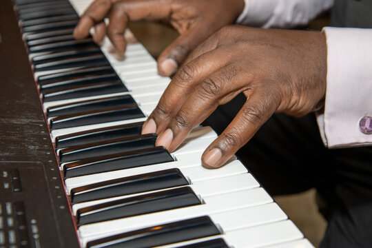 Fingers of an old African American man playing a keyboard piano wearing a black suit and pink shirt