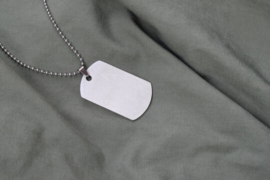 Silvery military beads with dog tag on dark green fatigue uniform