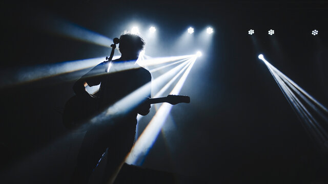 Silhouette of guitar player performinf on concert stage. Dark background, smoke, concert  spotlights