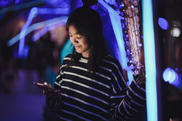 Asian young girl using a mobile phone in downtown