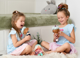 Happy laughing kid girls sisters in home dresses spend time together telling funny stories playing...