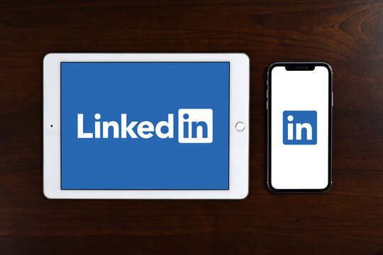 A business and employment-oriented online service that operates, LinkedIn logo displayed in full screen on iPad or tablet and iPhone or smartphone placed on wooden table.