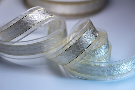 Full frame macro defocused background of silvery white brocade fabric ribbon with golden accent stitches on white background, with copy space