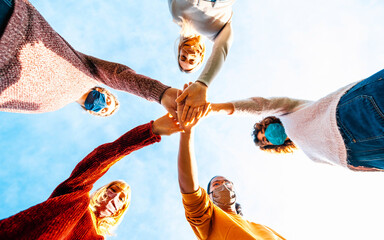 College students teamwork stacking hands - New normal lifestyle concept with people covered by face mask helping each other Wall mural