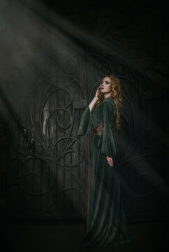 Beautiful young blonde girl in the medieval green dress. The queen looks away with her proud posture. The heaven light falls into darkness. The legends of Camelot and Lady Guinevere