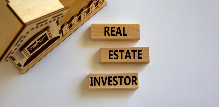 Real estate investor symbol. Wooden blocks with words 'Real estate investor' near miniature house. Beautiful white background. Business and real estate investor concept, copy space.