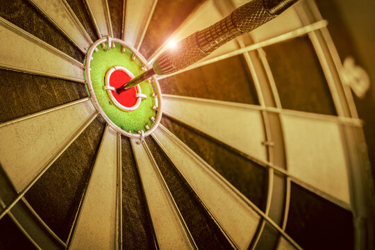 Red three darts arrows in the target center business goal concept, the game focuses on success, planning to be smart concept on retro filter tone