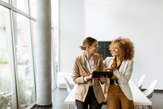 Women holding digital tablet and working in modern office