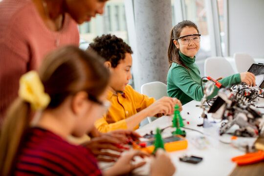 African American female science teacher with group of kids programming electric toys and robots at robotics classroom