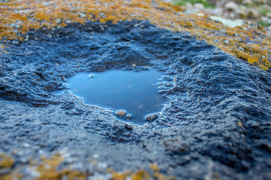 Close up view of puddle in the pit. Moss and mold on the stones.