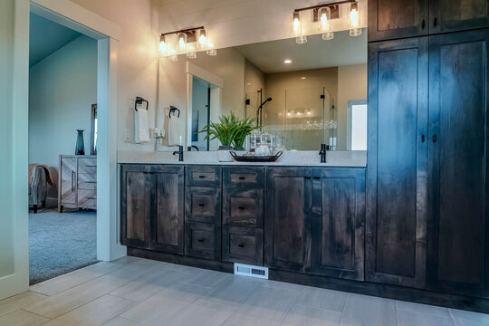 Double sink vanity unit with wooden cabinets and large mirror inside bathroom