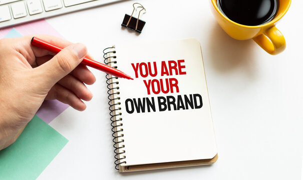 Hand with red pen. Coffee cup. Stick. Keyboard and white background. YOU ARE YOUR OWN BRAND sign in the notepad