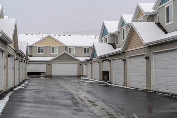 Wet and snowy paved road along white garage doors of apartments in winter view Fotobehang