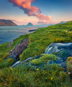Small creek on Hestur Island. Breathtaking sunrise on outskirts of Kirkjubour village, Faroe Islands, Denmark, Europe.  Beauty of nature concept background.