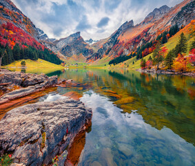 Beautiful autumn scenery. Colorful morning view of Swiss Alps. Santis peak reflected in the calm surface of pure water of lake. Stunning autumn scene of Seealpsee lake, Switzerland.