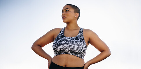 Curvy woman in sportswear with hands on hips