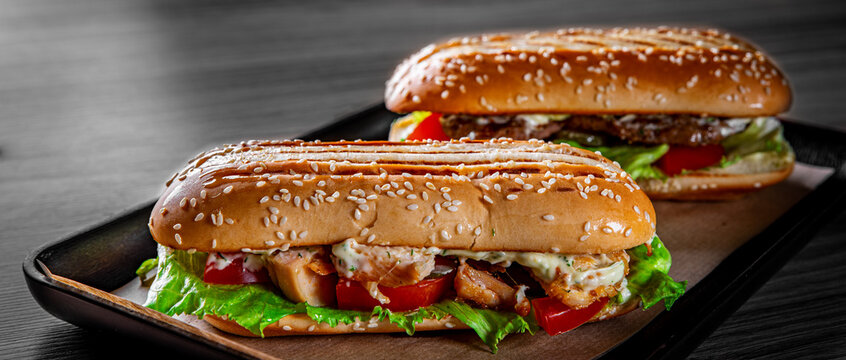 Two long submarine sandwiches with meat, cheese, bacon, tomatoes, lettuce, cucumbers and onions on black wooden table background