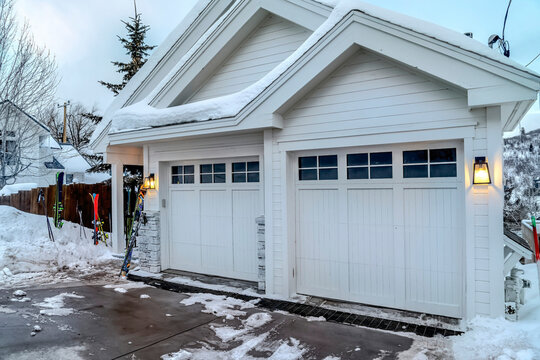 Home with white exterior walls and glass paned garage doors on a mountain town