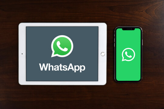 Telecommunications application specializes in providing text, video chat and voice calls over internet, WhatsApp logo displayed in full screen on iPad / tablet & iPhone / smartphone placed on a desk.