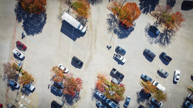 Top view grocery store parking lot with parked cars under colorful autumn leaves in Texas, USA