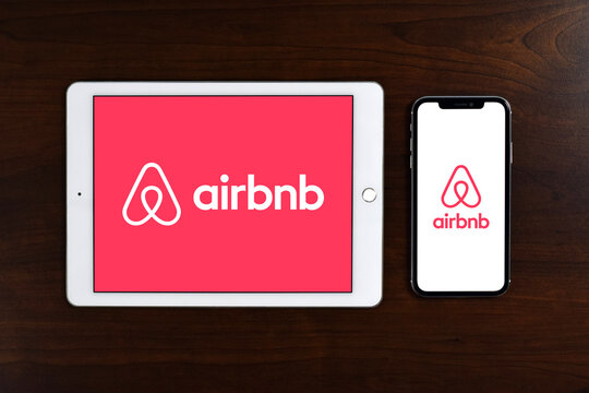 Airbnb logo displayed in full screen on iPad and iPhone placed on wooden table.  Airbnb is vacation rental online marketplace accessible to consumers on its website or via an app.