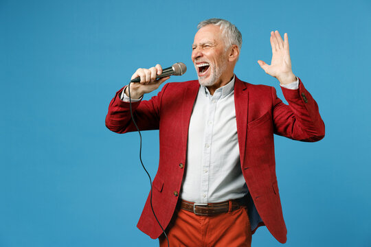 Cheerful elderly gray-haired mustache bearded business man wearing red jacket suit standing sing song in microphone spreading hands looking aside isolated on blue color background studio portrait.