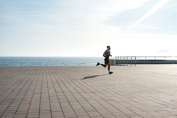 Fit young man running along seafront. Male runner jogging early in the morning. Fitness training outdoors. Workout during lockdown outside the gym. Fotobehang