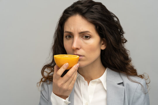 Sick business woman trying to sense smell of half fresh orange, has symptoms of Covid-19, corona virus infection - loss of smell and taste. One of the main signs of the disease. Studio grey background