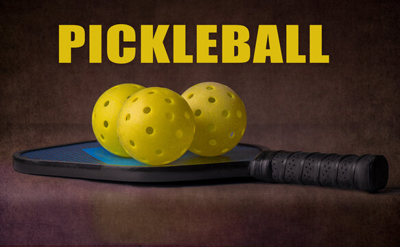 """Pickleball paddle and balls. With the word """"Pickleball"""" over a dark background. The sport of pickleball is America's fastest growing sport."""