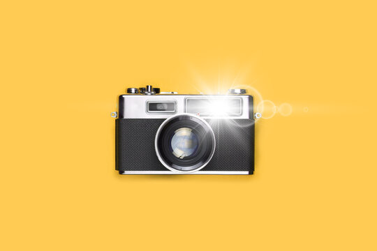 Old film camera with flash of light, yellow background