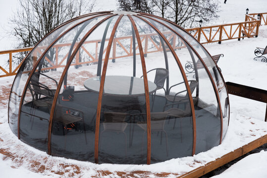 Transparent housing in the form of a dome, an igloo. It's winter, there's snow all around. Accommodation is waiting for guests