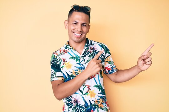 Young handsome latin man wearing summer clothes smiling and looking at the camera pointing with two hands and fingers to the side.