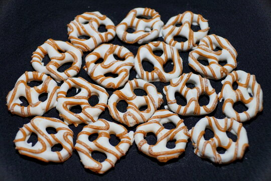 Yogurt pretzels with caramel drizzle on a black isolated background