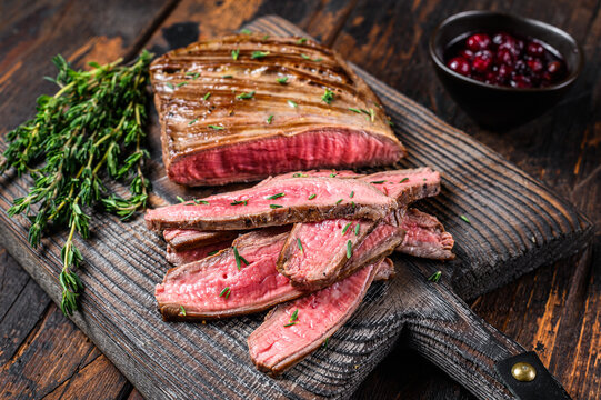 Barbecue sliced flank beef meat steak on a wooden cutting board. Dark wooden background. Top view