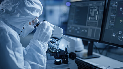 Research Factory Cleanroom: Engineer / Scientist wearing Coverall and Uses Microscope to Inspect...