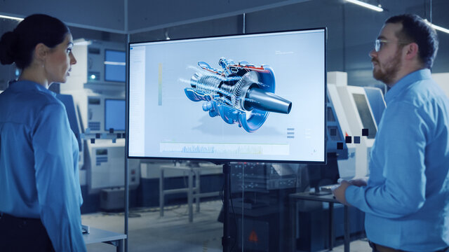 Office Meeting: Confident Female Engineer Talks to Project Manager, Watching Interactive Digital Whiteboard TV that Shows New Sustainable Eco-Friendly Engine 3D Concept. Modern Factory with Machinery