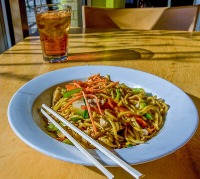 A dish of lo mein and glass of iced tea on a restaurant table