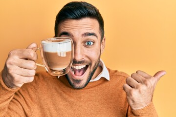Young hispanic man holding cup of coffee over eye pointing thumb up to the side smiling happy with...