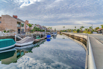 Overcast sky reflected on canal with docks and boats in Huntington Beach CA