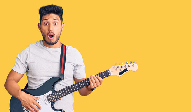 Handsome latin american young man playing electric guitar scared and amazed with open mouth for surprise, disbelief face