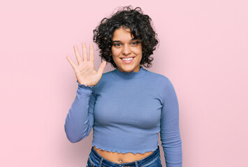 Young hispanic woman with curly hair wearing casual clothes showing and pointing up with fingers...