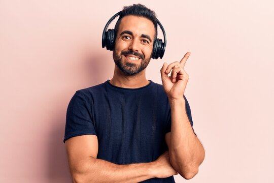 Young hispanic man listening to music using headphones smiling happy pointing with hand and finger to the side
