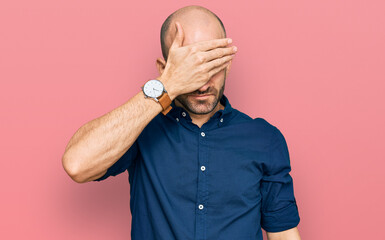 Young hispanic man wearing casual clothes covering eyes with hand, looking serious and sad....