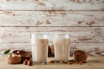 Glasses of tasty vegan milk on table