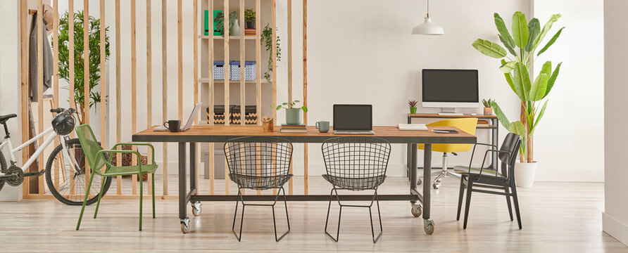 Modern and decorative office interior style with wooden long table, black metal chair, computer and laptop style.